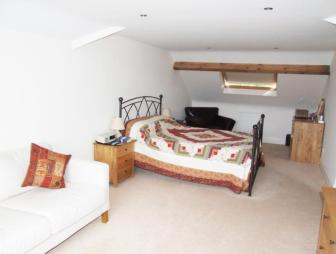 photo of beige white bedroom loft conversion master bedroom with gabled ceiling patchwork soft furnishings throw