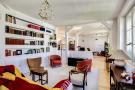 Open plan living room wooden floor bookshelves Postel-Vinay Paris