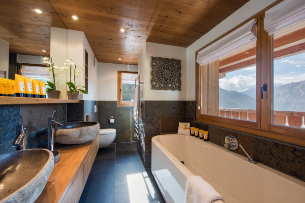 Master bathroom with mountain views from bath at Chalet Vermont in Verbier