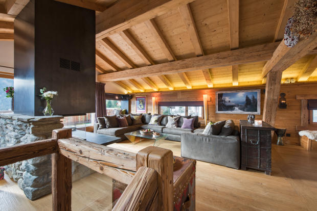 Living room with central fireplace at Chalet Vermont in Verbier