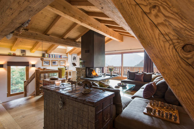 Open plan living room with central fireplace, kitchen and dining room at Chalet Vermont in Verbier