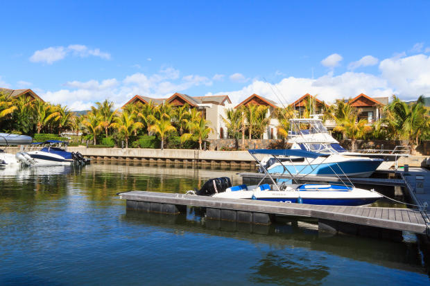 Power boats moored outside duplexes at La Balise Marina in Mauritius