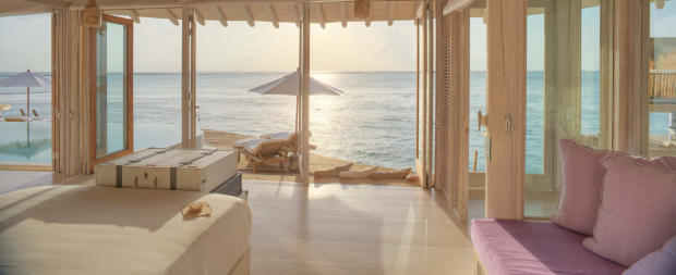 Bedroom view of sea in an over water villa at Soneva Jani during sunrise