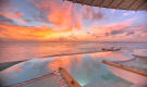Sunset over pool and ocean from over water villa at Soneva Jani