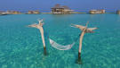 Water hammock in the sea with over water villas in the background at Soneva Jani