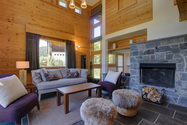 Spacious living room with fireplace and double height ceiling at Chalet Lievre in Verbier