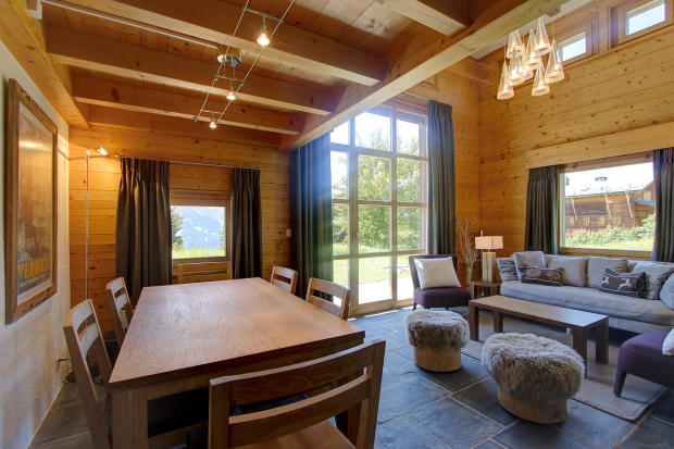 Dining room and living room with patio doors at Chalet Lievre in Verbier