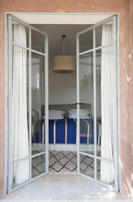 View into master bedroom through French doors to terrace at Villa Jardin