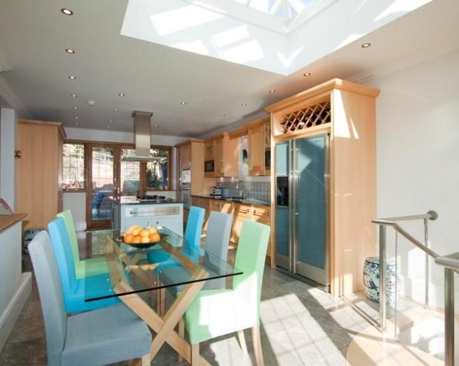 photo of colourful open plan beige blue white kitchen with skylight