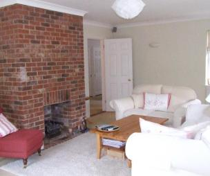photo of beige brown pink white lounge with brick fireplace fireplace