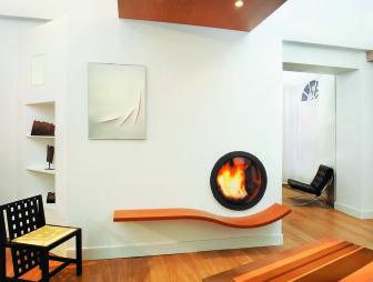 photo of designer modern odd shapes diligence international living room with in-wall fire fireplace porthole wood burner