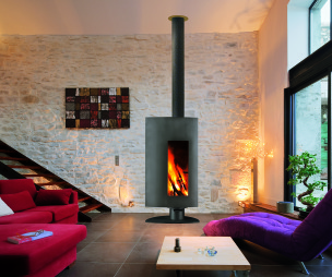 photo of arty designer stone diligence international living room with feature fireplace staircase stairs wood burner fire sculpture and funky sofa furniture