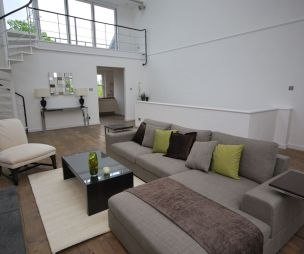 photo of contemporary designer double height light modern neutral open plan green grey white hello of mayfair balcony living room lounge with staircase stairs and corner sofa designer furniture designer sofa furniture sofa