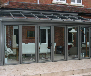 photo of traditional grey breckenridge conservatory garden with folding sliding doors and patio