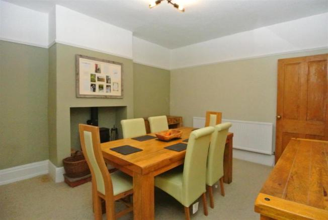 The dining room has a cosy multi fuel stove