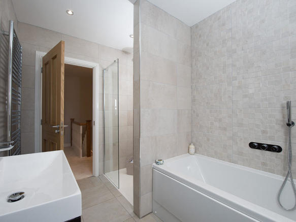Extensively tiled family bathroom with separate shower cubicle