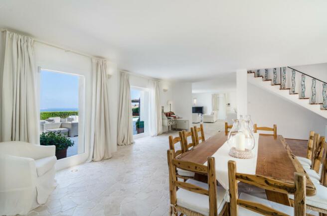 Dining room open plan stone floor french doors Villa Cassedda Porto Cervo Sardinia