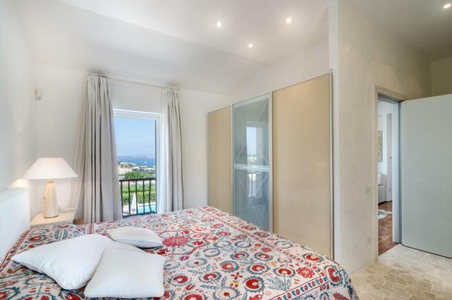 Bedroom ensuite balcony doors stone floor Villa Cassedda Porto Cervo Sardinia