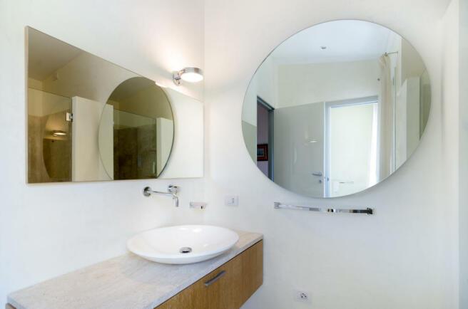 Bathroom sink circle mirror Villa Cassedda Porto Cervo Sardinia
