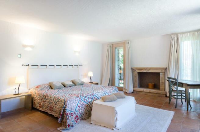 Bedroom tiled floor fireplace french doors Villa Cassedda Porto Cervo Sardinia