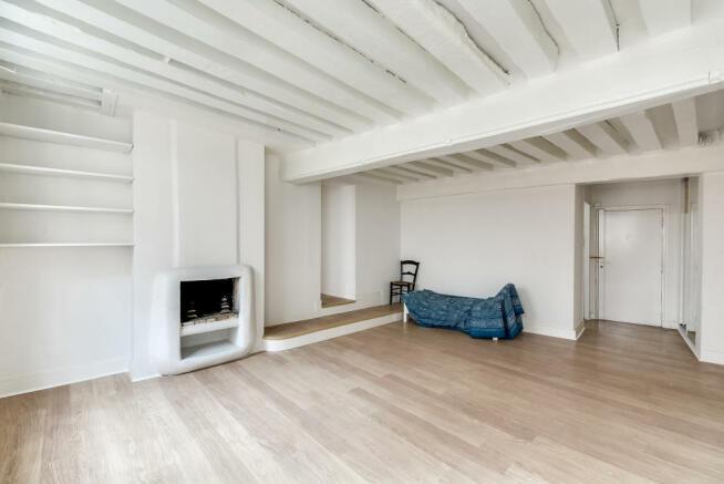 Living room white exposed beams wood floor fireplace Quincampoix Paris