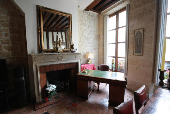 Dining room stone fireplace tiled floor wooden beams Rue Frederic Sauton Paris