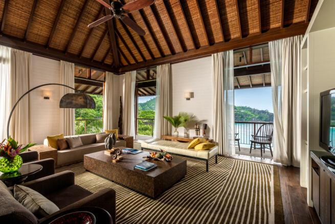 Living room wood floor balcony doors sea view ocean Four Seasons Seychelles