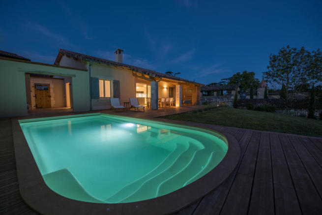 External facade of villa with pool at night
