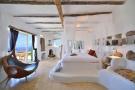Bedroom master exposed beams marble floor french doors Lia Mykonos