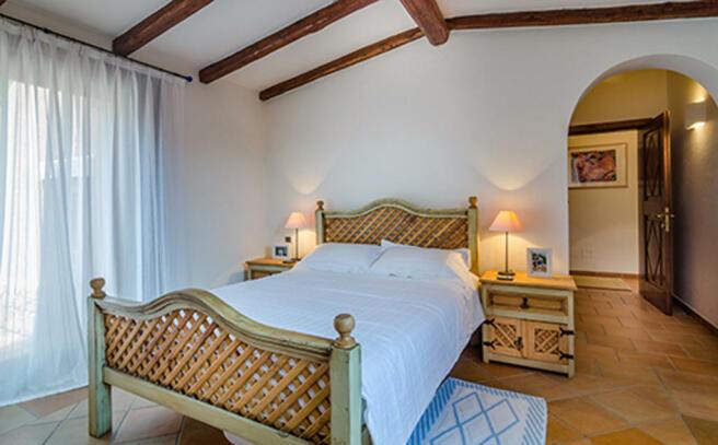 Bedroom exposed wood beams tiled floor Villa  Li Liccioli Sardinia