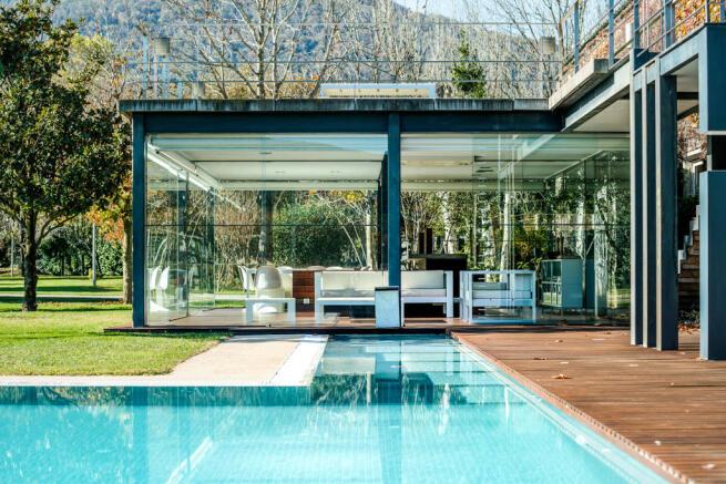 Swimming pool covered dining area garden full height windows Finca Mia Vall d'en Bas Girona