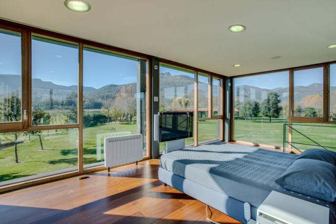 Living room full height windows wood floor Finca Mia Vall d'en Bas Girona