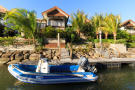 Speedboat moored outside home at La Balise Marina in Mauritius