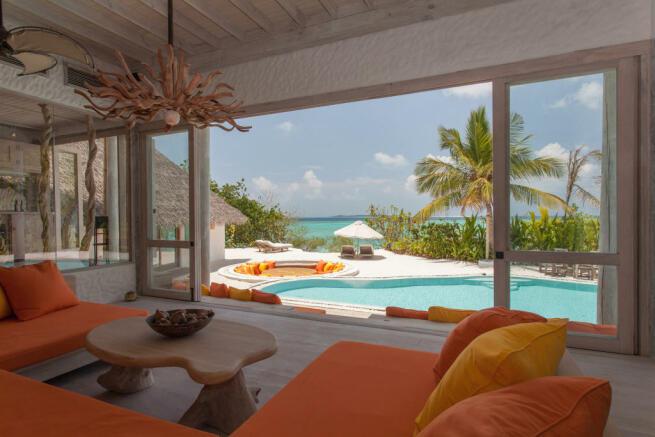 Living room sliding doors swimming pool Villa Sunrise at Soneva Fushi Maldives