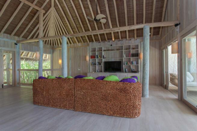 Living room large full height ceiling wood Villa Sunrise at Soneva Fushi Maldives
