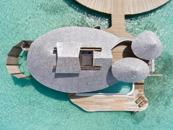 Aerial view of over water villa with retractible roof at Soneva Jani