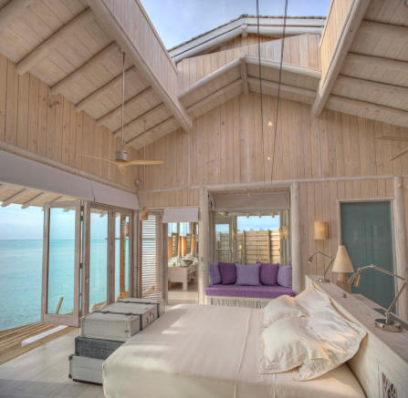 Master bedroom with retractible roof inside over water villa at Soneva Jani