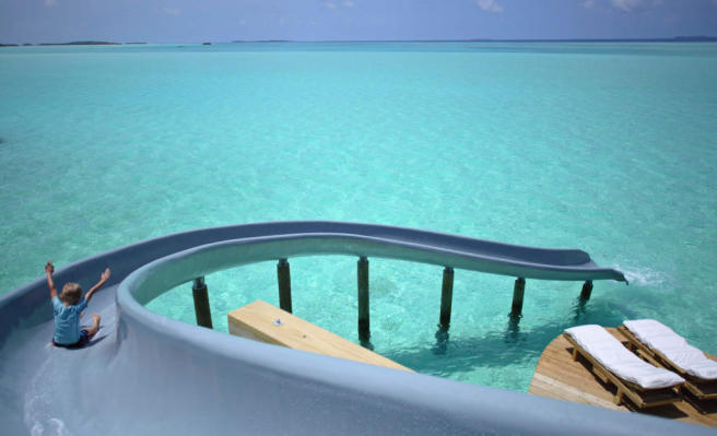 Waterslide from over water villa into sea at Soneva Jani