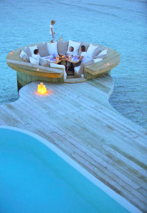 Open air dining area at over water villa at Soneva Jani