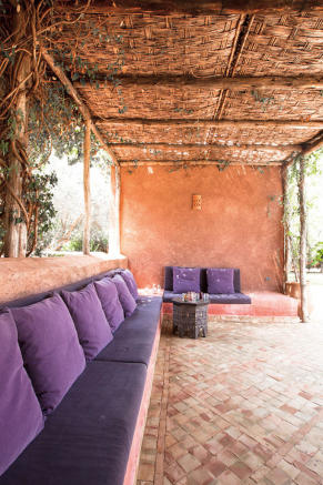 Outdoor covered seating with purple cushions at Villa Jardin