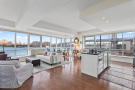 Open plan living room and kitchen with city, water and bridge views at 440 Kent Avenue in Brooklyn, New York