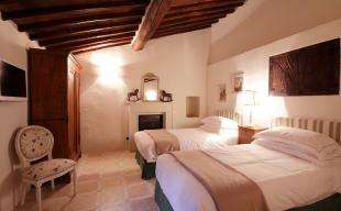 Bedroom twin tiled floor exposed beams wood Tenuta Cipressino Tuscany