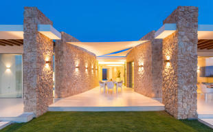 Covered terrace with dining area at night at Villa Roberta in Ibiza