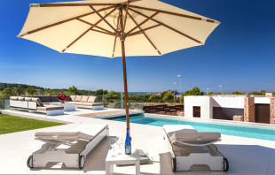 Outdoor pool with parasol in terrace area at Villa Roberta in Ibiza