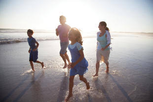 Family having fun on the beach near St Antoine Mauritius