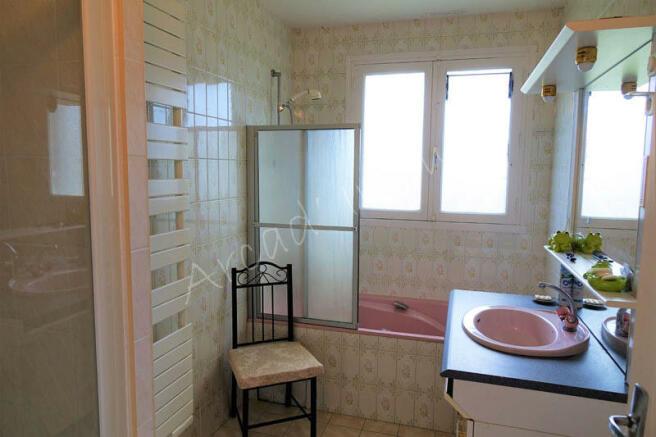 A bathroom with bath and shower