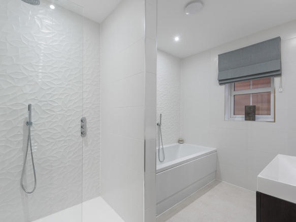 Family bathroom with separate shower and extensive Porcelanosa tiling