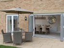 Bi-fold doors leading to paved patio and rear garden