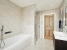 Extensively tiled family bathroom with separate shower