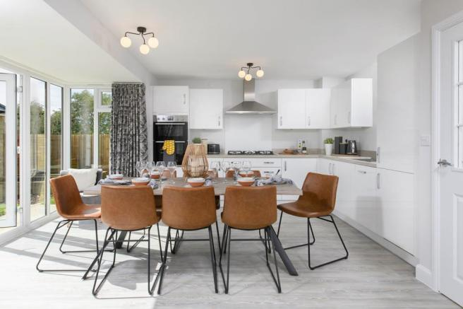 Open-plan kitchen/dining area with glazed bay leading onto garden - Millford style home